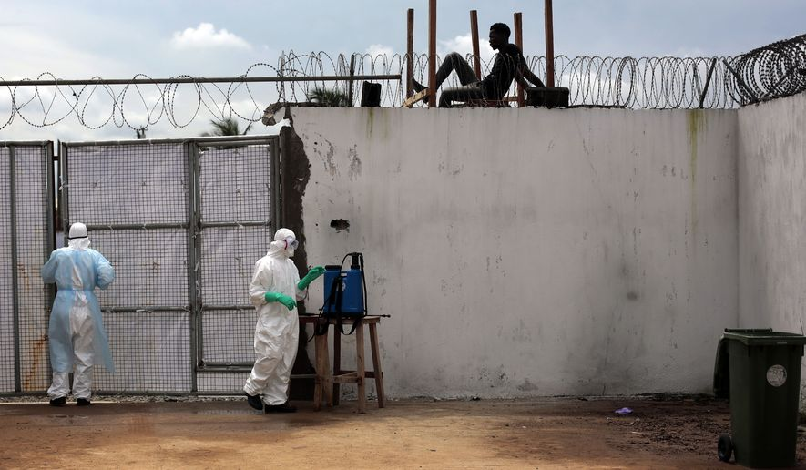 Health workers stand outside the Island Clinic Ebola isolation and treatment center in Monrovia, Liberia, Friday Sept. 26, 2014.  The outbreak of Ebola has overwhelmed the weak health systems of some of the world's poorest countries - there aren't enough doctors and nurses or even clinics to treat the spiraling number of cases.(AP Photo/Jerome Delay)