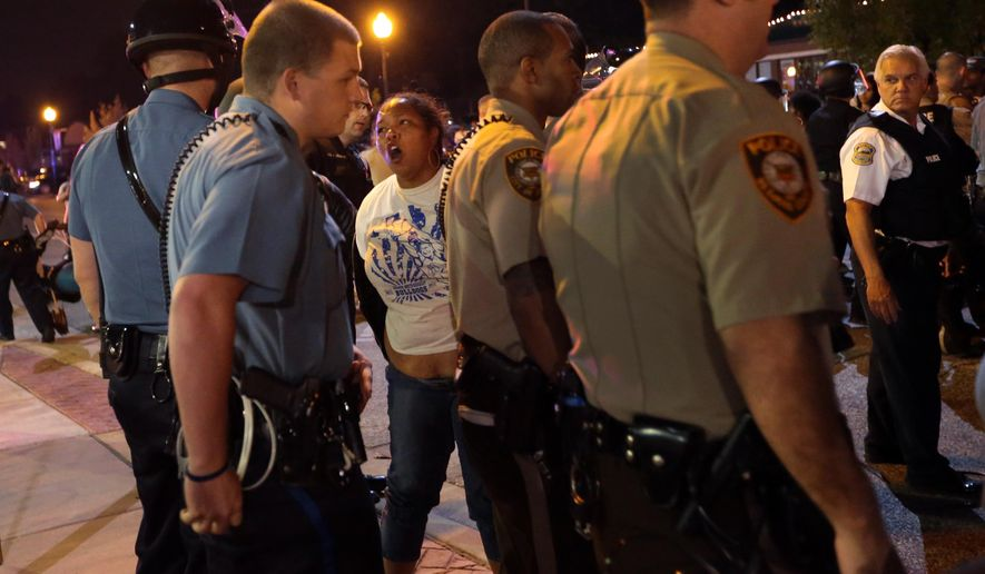 A woman is arrested by police officers in front of the Ferguson Police Department, on Thursday, Sept. 25, 2014. (AP Photo/St. Louis Post-Dispatch, Robert Cohen)