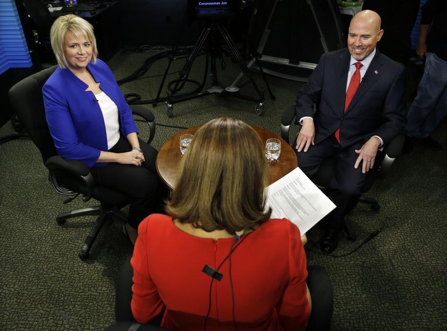 Candidates in New Jersey's contentious and close 3rd Congressional District, Democrat Aimee Belgard, left, and Republican Tom MacArthur, right, appear together to answer questions in joint interview on NJTV with host Marie DeNoia Aronsohn, center, in Trenton, N.J. on Friday, Sept. 26, 2014. (AP Photo/Mel Evans)