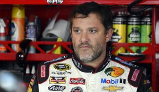 In this Sept. 13, 2014, file photo, Tony Stewart looks out from his garage during practice for the NASCAR Sprint Cup series auto race at Chicagoland Speedway in Joliet, Ill. A grand jury decided against charging Stewart in the death of Kevin Ward Jr. on a dirt track last month in upstate New York. Stewart took three weeks off from racing after the crash. (AP Photo/Paul J. Bergstrom, File)