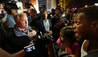 Ferguson Police Chief Tom Jackson, left, speaks before protesters in front of the Ferguson Police Department, on Thursday, Sept. 25, 2014. (AP Photo/St. Louis Post-Dispatch, Robert Cohen)
