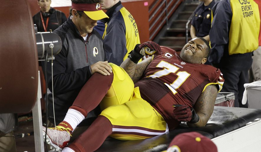 Washington Redskins tackle Trent Williams (71) is treated along the sidelines after an injury during the second half of an NFL Thursday night football game against the New York Giants in Landover, Md., Thursday, Sept. 25, 2014. The Giants defeated the Redskins 45-14. (AP Photo/Patrick Semansky)