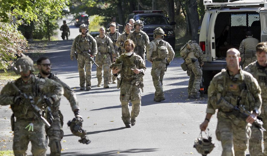 FBI along with various state police officers exit a wooded area at Buck Hill Falls in Barrett Township, Pa., where the search for Eric Frein continues Friday, Sept 26, 2014. Frein is suspected of fatally shooting a state trooper and wounding another at the Blooming Grove state police barracks two weeks ago. (AP Photo/Scranton Times & Tribune, Michael J. Mullen)