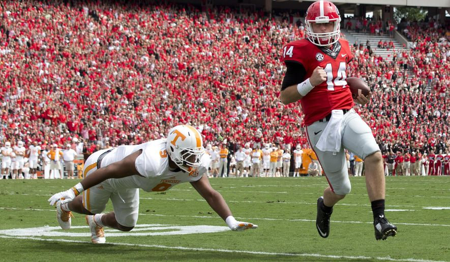 Georgia quarterback Hutson Mason (14) out runs Tennessee defensive end Derek Barnett (9) to the end zone for a touchdown in the first half of an NCAA college football game, Saturday, Sept. 27, 2014, in Athens, Ga. (AP Photo/John Bazemore)