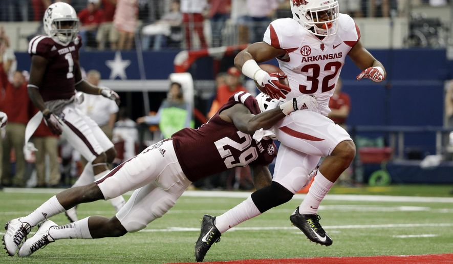 Texas A&M defensive back Deshazor Everett is unable to stop Arkansas running back Jonathan Williams (32) from scoring on a running play in the first half of an NCAA college football game, Saturday, Sept. 27, 2014, in Arlington, Texas. (AP Photo/Tony Gutierrez)
