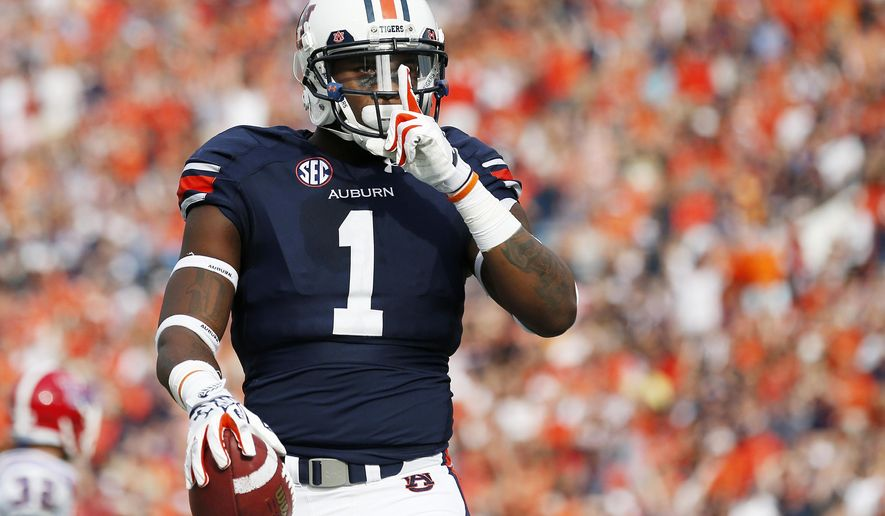 Auburn wide receiver D'haquille Williams (1) gestures after scoring a touchdown against Louisiana Tech defensive back Xavier Woods and Louisiana Tech defensive back Kentrell Brice during the first half of an NCAA college football game Saturday, Sept. 27, 2014, in Auburn, Ala.(AP Photo/Brynn Anderson)