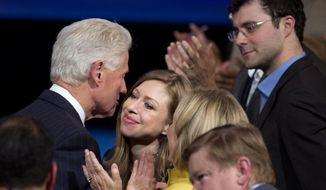Former President Bill Clinton hugs his daughter, Chelsea Clinton, during the closing session of the Clinton Global Initiative in New York Wednesday, Sept. 24, 2014. At right is Chelsea's husband, Marc Mezvinsky. (AP Photo/Craig Ruttle)