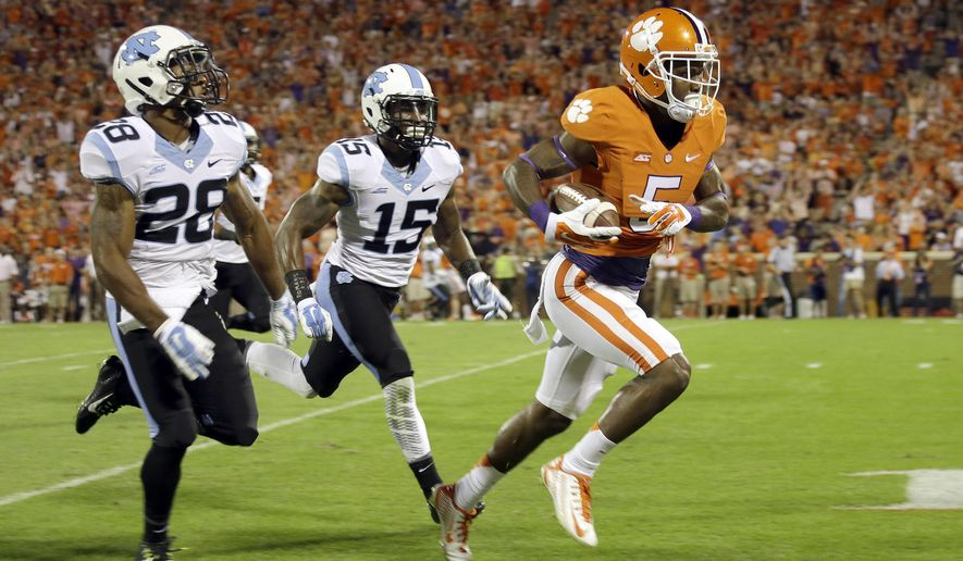 Clemson's Germone Hopper (5) makes his way to the end zone for his second touchdown of the first half as North Carolina's Brian Walker (28) and Donnie Miles (15) gives chase during an NCAA college football game in Clemson, S.C., Saturday Sept. 27, 2014. (AP Photo/Bob Leverone)