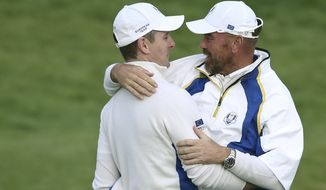 Europe's Thomas Bjorn congratulates  Justin Rose on winning the hole and halving the match on the 18th green at the  end of  the foursomes match on the second day of the Ryder Cup golf tournament at Gleneagles, Scotland, Saturday, Sept. 27, 2014. (AP Photo/Scott Heppell)