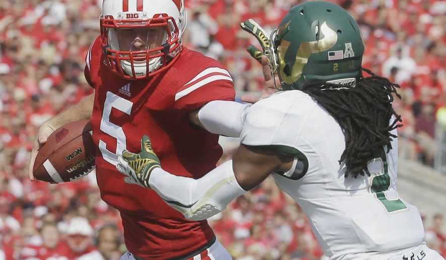Wisconsin's Tanner McEvoy tries to run past South Florida's Jamie Byrd during the first half of an NCAA college football game, Saturday, Sept. 27, 2014, in Madison, Wis. (AP Photo/Morry Gash)