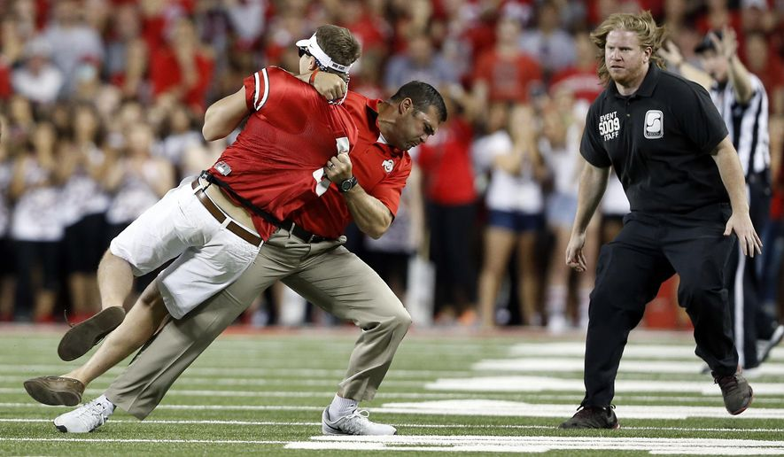 Ohio State strength and conditioning coach Anthony Schlegel tackles a person who ran onto the field during the second quarter of the NCAA college football game between Ohio State on Saturday, Sept. 27, 2014, in Columbus, Ohio. (AP Photo/The Columbus Dispatch, Adam Cairns)