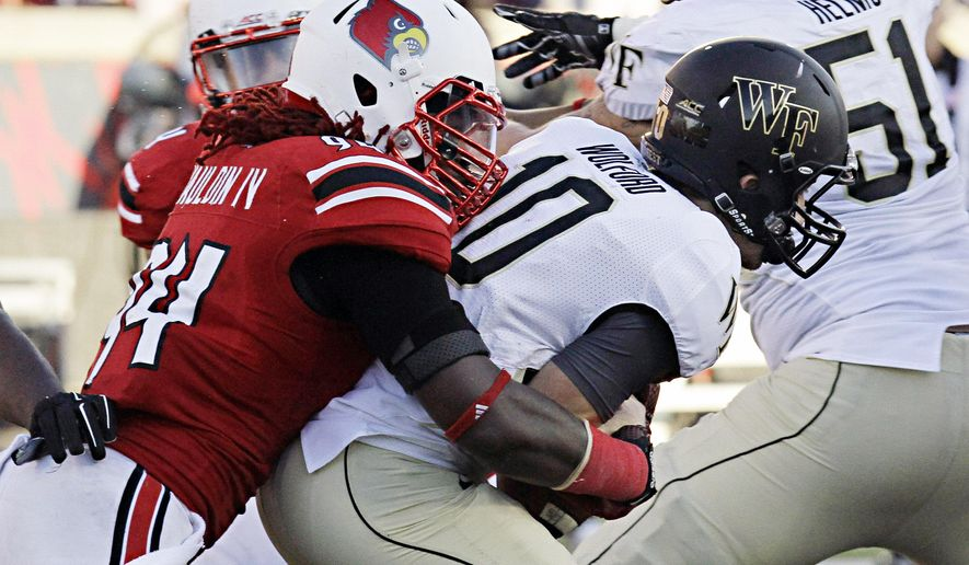 Louisville linebacker Lorenzo Mauldin, IV (94) drops Wake Forest quarterback John Wolford (10) for a loss late in the second half of their NCAA college football game in Louisville, Ky., Saturday, Sept. 27, 2014. Louisville came from behind to beat Wake Forest 20-10. (AP Photo/Garry Jones)