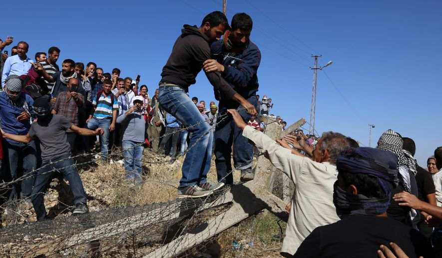 "In this Friday, Sept. 26, 2014 photo, Kurds from Turkey, left, and Syria break down the barbed wire at the Turkey-Syria border near Suruc, Turkey. Turkish President Recep Tayyip Erdogan said Friday that a ""no-fly zone"" should be created in Syria to protect part of it from attacks by Syria's air force. In his comments to reporters on his return from the U.N. General Assembly in New York, Erdogan did not specify where such a zone should be located. (AP Photo/Burhan Ozbilici)"