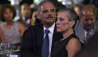 Attorney General Eric Holder, center, sits with his wife Sharon Malone, right, as they wait for President Barack Obama to speak at the Congressional Black Caucus Foundation's 44th Annual Legislative Conference Phoenix Awards Dinner in Washington, Saturday, Sept. 27, 2014. Obama told the audience that the mistrust of law enforcement that was exposed after the fatal police shooting in Ferguson, Missouri, has a corrosive effect on all of America, not just on black communities. (AP Photo/Susan Walsh)