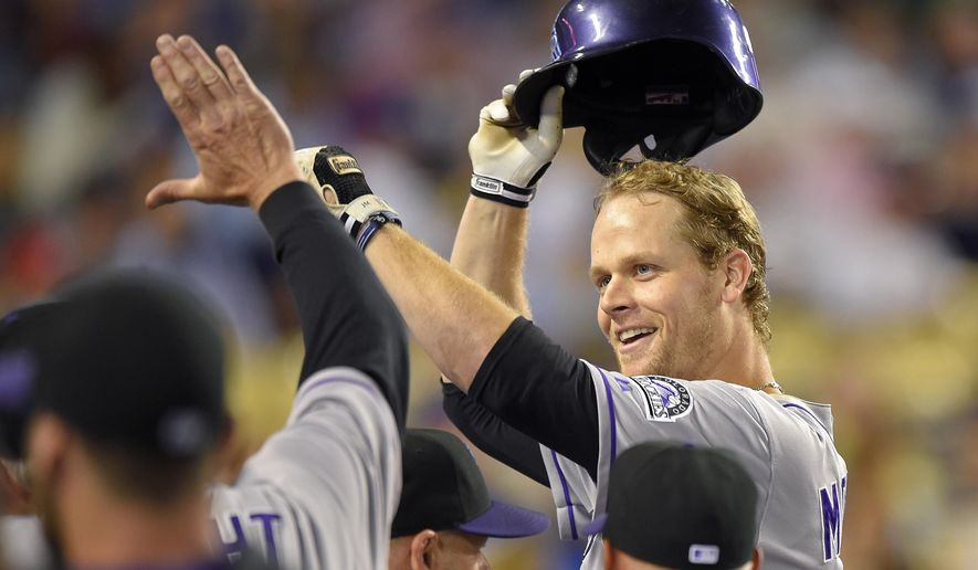 Colorado Rockies' Justin Morneau, right, is congratulated by teammates after hitting a two-run home run during the third inning of a baseball game against the Los Angeles Dodgers, Friday, Sept. 26, 2014, in Los Angeles. (AP Photo/Mark J. Terrill)