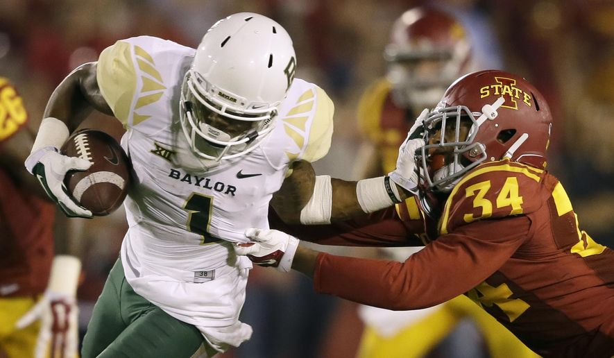 Baylor running back Corey Coleman tries to break a tackle by Iowa State defensive back Nigel Tribune (34) during the second half of an NCAA college football game, Saturday, Sept. 27, 2014, in Ames, Iowa. Baylor won 49-28. (AP Photo/Charlie Neibergall)