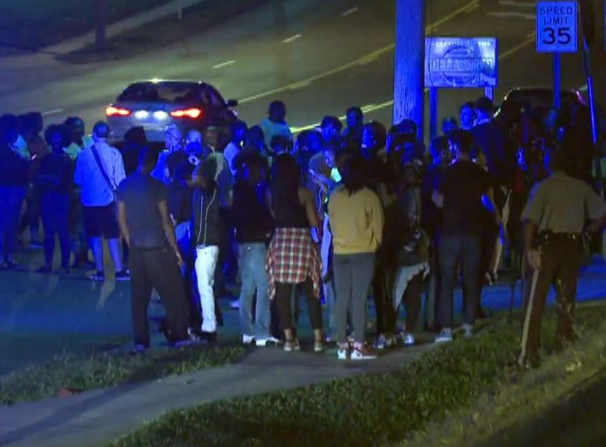 In this framegrab image courtesy of KSDK-TV a crowd gathers near the scene where a police officer was shot in the arm Saturday night Sept. 27, 2014 in Ferguson, Missouri. The officer was shot in the arm and is expected to survive, St. Louis County Police Chief Jon Belmar said. (AP Photo/KSDK-TV)