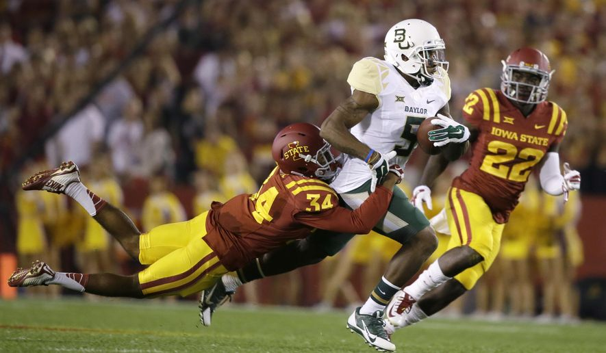 Baylor wide receiver Antwan Goodley (5) runs from Iowa State defensive backs Nigel Tribune, left, and T.J. Mutcherson, right, after making a reception during the first half of an NCAA college football game, Saturday, Sept. 27, 2014, in Ames, Iowa. (AP Photo/Charlie Neibergall)