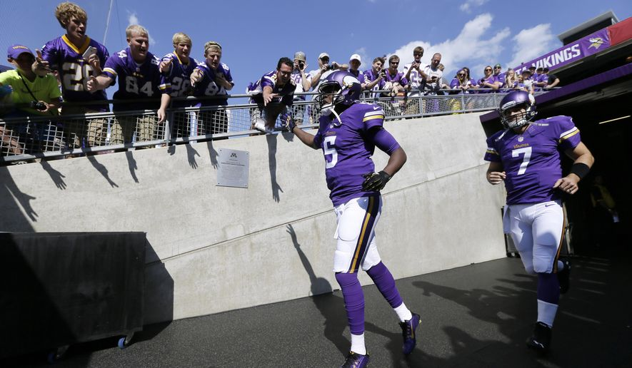 Minnesota Vikings quarterbacks Teddy Bridgewater (5) and Christian Ponder (7) run to the field for warmups before the Vikings' NFL football game against the Atlanta Falcons, Sunday, Sept. 28, 2014, in Minneapolis. (AP Photo/Charlie Neibergall)