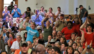 Area residents cheer as statements are made  during a presentation by federal officials involved in the placement of immigrant children at St Paul's College in Lawrenceville, Va., Thursday, June 19, 2014. The program is on hold pending comments from local residents (AP Photo/Steve Helber)