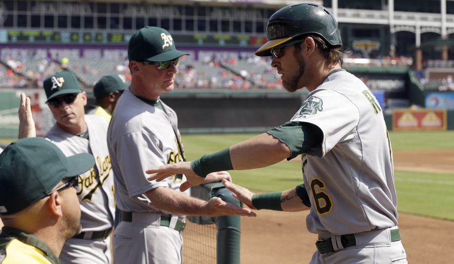 Oakland Athletics Josh Reddick, right, is congratulated by manager Bob Melvin after scoring during the second inning of a baseball game against the Texas Rangers in Arlington, Texas, Sunday, Sept. 28, 2014. Reddick scored on a single by teammate Stephen Vogt. (AP Photo/LM Otero)