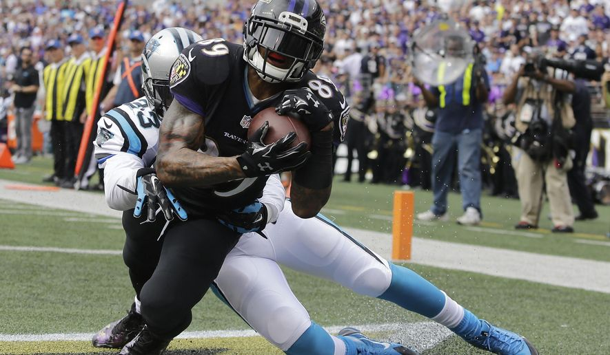 Baltimore Ravens wide receiver Steve Smith (89) pulls in a touchdown pass under pressure form Carolina Panthers cornerback Melvin White (23) during the first half of an NFL football game in Baltimore, Sunday, Sept. 28, 2014. (AP Photo/Patrick Semansky)