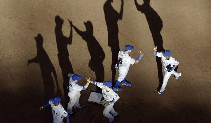The Chicago Cubs celebrate a 5-2 win over the Milwaukee Brewers in a baseball game Sunday, Sept. 28, 2014, in Milwaukee. (AP Photo/Morry Gash)