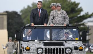New Jersey Gov. Chris Christie New Jersey Adjutant General Brig. Gen. Michael Cunniff,right, ride in a vehicle as they review troops during the New Jersey National Guard's annual Military Review Sunday, Sept. 28, 2014, in Sea Girt, N.J. (AP Photo/Mel Evans)