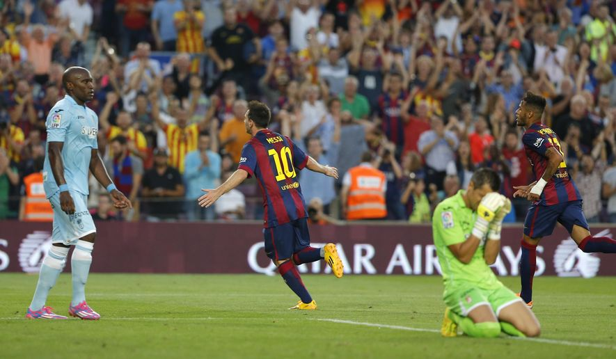 Barcelona's Lionel Messi from Argentina, center, celebrates scoring his side's sixth goal during a Spanish La Liga soccer match between F.C. Barcelona and Granada C.F. at the Camp Nou stadium in Barcelona, Spain, Saturday, Sept. 27, 2014. (AP Photo/Emilio Morenatti)
