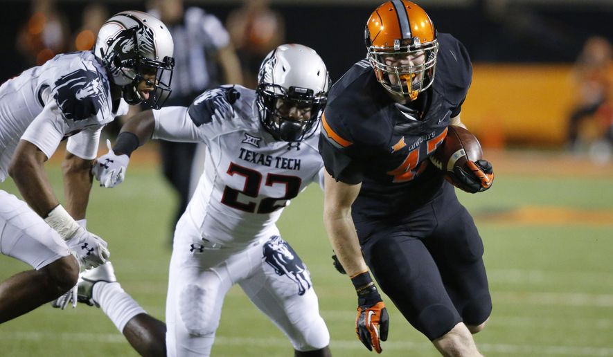 Oklahoma State tight end Blake Jarwin (47) carries a Daxx Garman pass into the end zone in front of Texas Tech safety Derrick Dixon (22) and defensive back Justis Nelson, left, in the third quarter of an NCAA college football game in Stillwater, Okla., Thursday, Sept. 25, 2014. Oklahoma State won 45-35. (AP Photo/Sue Ogrocki)
