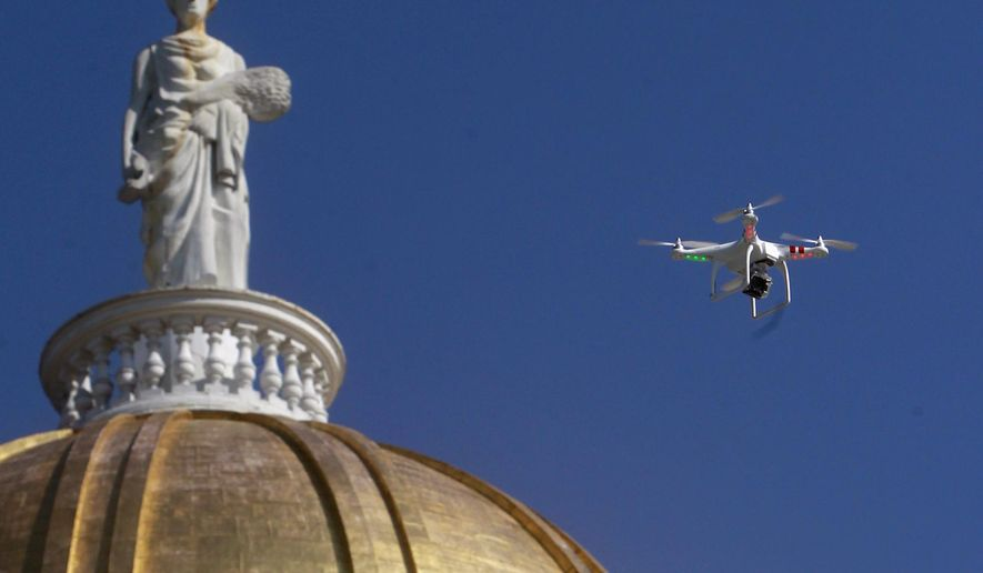 FILE - In this Sept. 17, 2013 file photo, a drone is flown over the Statehouse in Montpelier, Vt., in support of legislation by the state chapter of the American Civil Liberties Union that would regulate surveillance of private citizens by law enforcement agencies. A hearing is scheduled for Oct. 21, 2014, on a different proposal by the Fish and Wildlife Board, which governs hunting in the state, to preemptively ban hunting with drones or from other types of aircraft. (AP Photo/Toby Talbot, File)