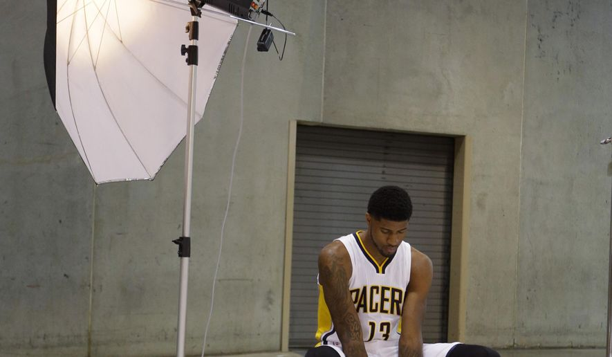 Indiana Pacers forward Paul George dribbles a ball as he waits to have his photo taken during NBA basketball media day in Indianapolis, Monday, Sept. 29, 2014. (AP Photo/Michael Conroy)