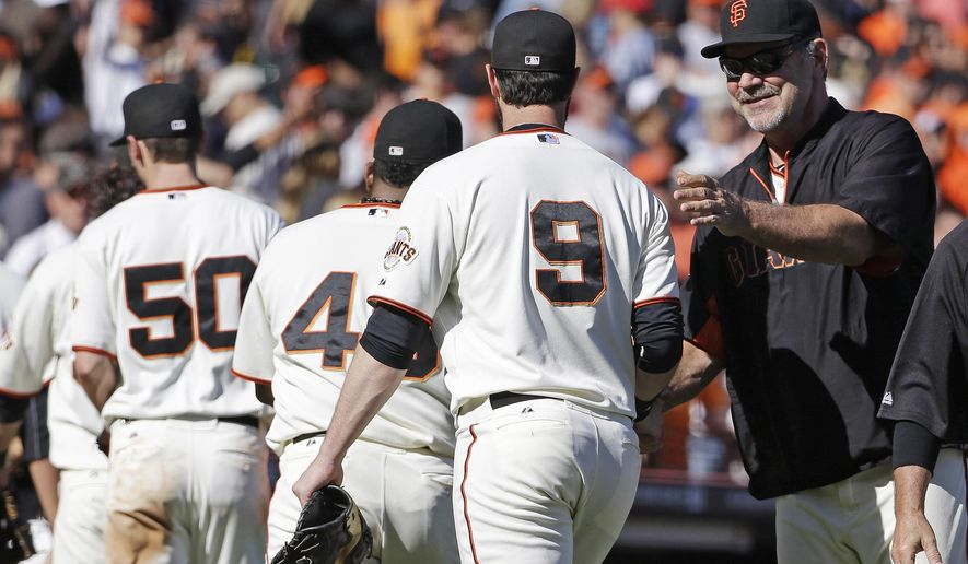 San Francisco Giants manager Bruce Bochy, right, greets Brandon Belt (9) at the end of their baseball game against the San Diego Padres Saturday, Sept. 27, 2014, in San Francisco. San Francisco won the game 3-1. (AP Photo/Eric Risberg)