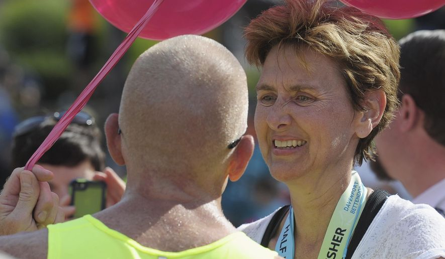 In this Sunday, Sept. 28, 2014 photo, Sue Druckmiller, Lake of the Hills, Ill., has a teary reunion with Jeff Blakeman, of Kansas, at the Quad Cities Marathon in Moline, Ill. Blakeman had a heart attack during last year's marathon and Druckmiller, a nurse, stopped her race and administered CPR until help arrived. Blakeman was back to finish the last seven miles he didn't complete last year.  (AP Photo/The Dispatch, Todd Welvaert)  QUAD CITY TIMES OUT