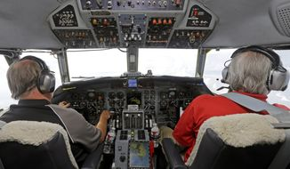 In this Aug. 15, 2014 photo, Captain Randy Moore, left, and co-pilot Mark Johnson, right, fly a Convair 580 test plane during a flight demo of the Honeywell InturVue weather radar over Florida. Advances in radar are helping pilots avoid storms that can injure and upset passengers and even damage planes. (AP Photo/Alan Diaz)