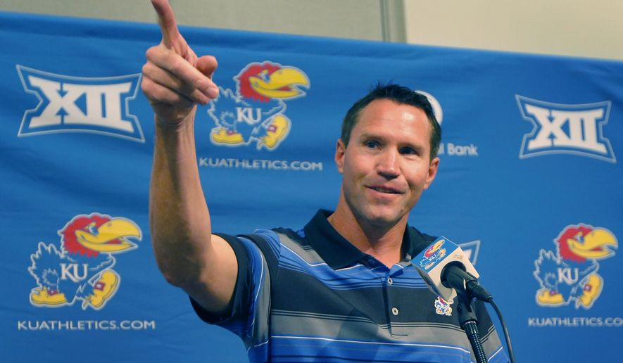 Kansas interim head football coach Clint Bowen points to his wife while answering a question during an NCAA college football news conference in Lawrence, Kan., Monday, Sept. 29, 2014. Bowen replaces Charlie Weis, who was fired after Saturday's 23-0 loss to Texas. (AP Photo/Orlin Wagner)