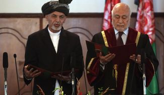Afghan President Ashraf Ghani Ahmadzai, left, is sworn in by Chief Justice Abdul Salam Azimi, during his inauguration ceremony at the presidential palace in Kabul, Afghanistan, Monday, Sept. 29, 2014. Ghani Ahmadzai He replaces Hamid Karzai in the country's first democratic transfer of power since the 2001 U.S.-led invasion toppled the Taliban. (AP Photo/Rahmat Gul)