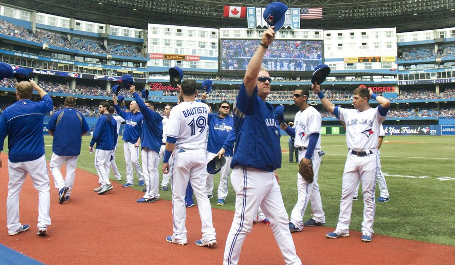 Toronto Blue Jays players and coaches step onto the field to acknowledge the fans during the fourth inning against the Baltimore Orioles in a baseball game Sunday, Sept. 28, 2014, in Toronto. (AP Photo/The Canadian Press, Fred Thornhill)