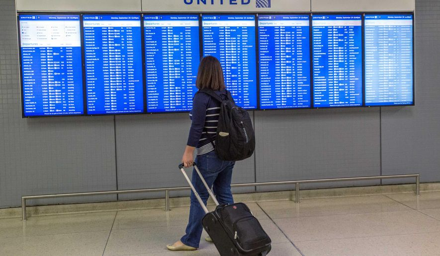A traveler looks at a flight departure board Monday, Sept. 29, 2014, at O'Hare International Airport in Chicago. The Federal Aviation Administration said Monday it is reviewing security practices and how it deals with unexpected incidents throughout its air traffic control facilities following last week's fire at a Chicago-area air traffic facility. (AP Photo/Teresa Crawford)