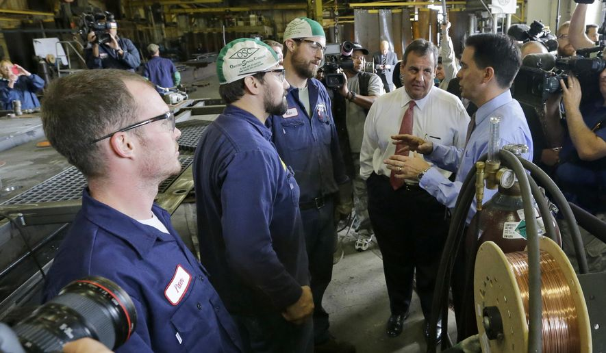 New Jersey Gov. Chris Christie and Wisconsin Gov. Scott Walker, right, talk with employees at Empire Bucket as Walker campaigns in Hudson, Wis., Monday, Sept. 29, 2014.   (AP Photo/Ann Heisenfelt)