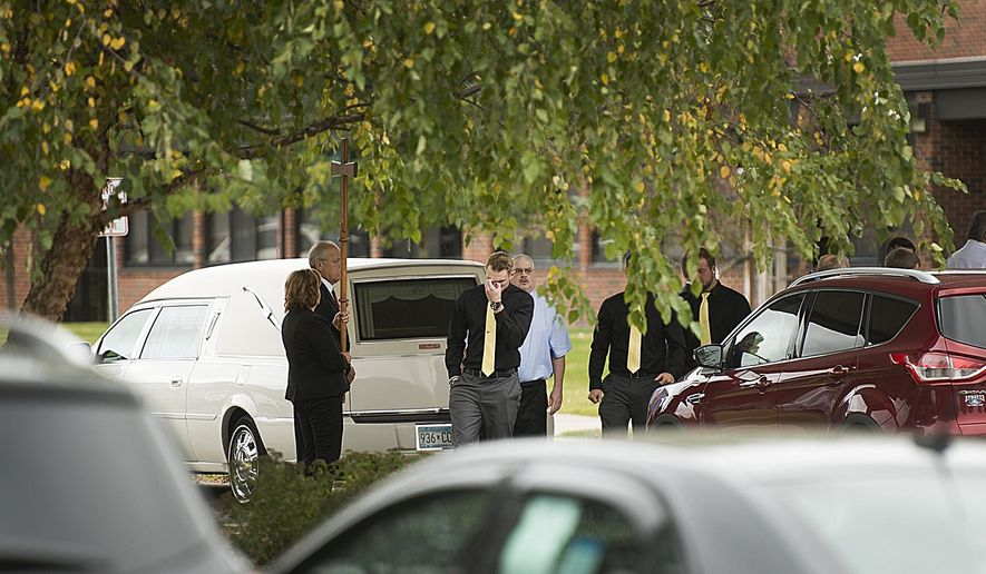 People leave a funeral service for 18-year-old Thomas Bearson, Monday, Sept. 29, 2014 at St. Francis Xavier Catholic Church in Sartell, Minn. The North Dakota State University student found slain in Moorhead has been laid to rest as authorities search for his killer. (AP Photo/The St. Cloud Times, Jun-Kai Teoh)
