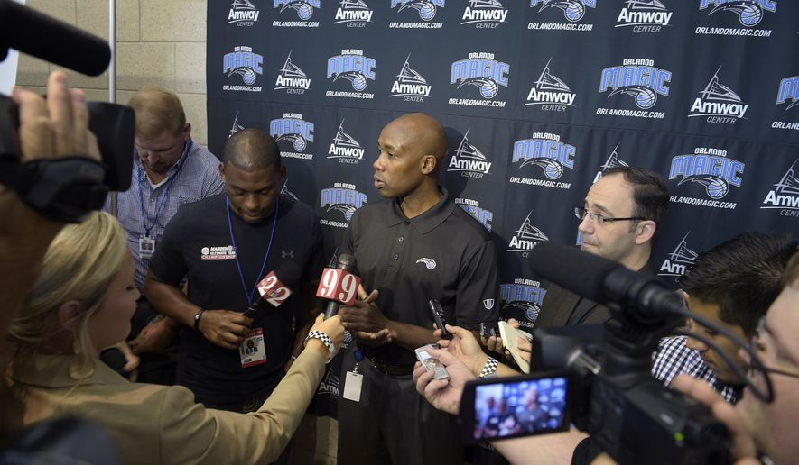 Orlando Magic head coach Jacque Vaughn, center, answers questions from reporters during NBA basketball media day in Orlando, Fla., Monday, Sept. 29, 2014. (AP Photo/Phelan M. Ebenhack)