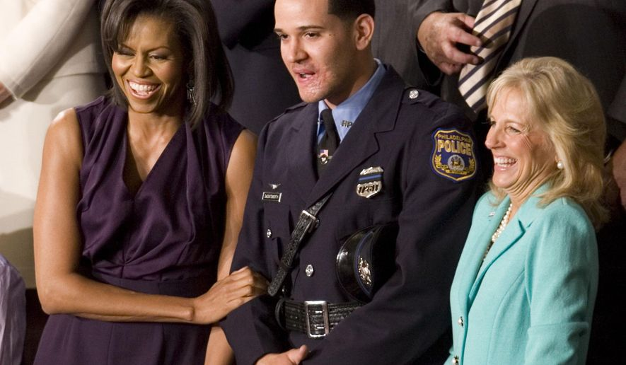 FILE - In a Feb. 24, 2009 file photo, first Lady Michelle Obama and Jill Biden, wife of Vice President Joe Biden, stand in the gallery with Philadelphia Police Officer Richard DeCoatsworth during President Barack Obama's address to a joint session of Congress in Washington. DeCoatsworth was freed Monday,, Sept. 29, 2014, after more than a year in jail on human trafficking, rape, drug and other charges. Philadelphia prosecutors dropped the charges after defense attorney George Parry questioned the accusers' credibility in pretrial filings. (AP Photo/Evan Vucci, File)