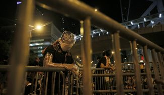 Wrapped in plastic as protection from pepper spray, a student protester stands behind a makeshift barrier blocking main streets in the business district of Hong Kong Monday. (Associated Press)