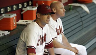 Arizona Diamondbacks manager A. J. Hinch and coach Matt Williams, right, sit in the dugout prior to a baseball game against the Colorado Rockies Friday, June 4, 2010, in Phoenix. (AP Photo/Matt York)