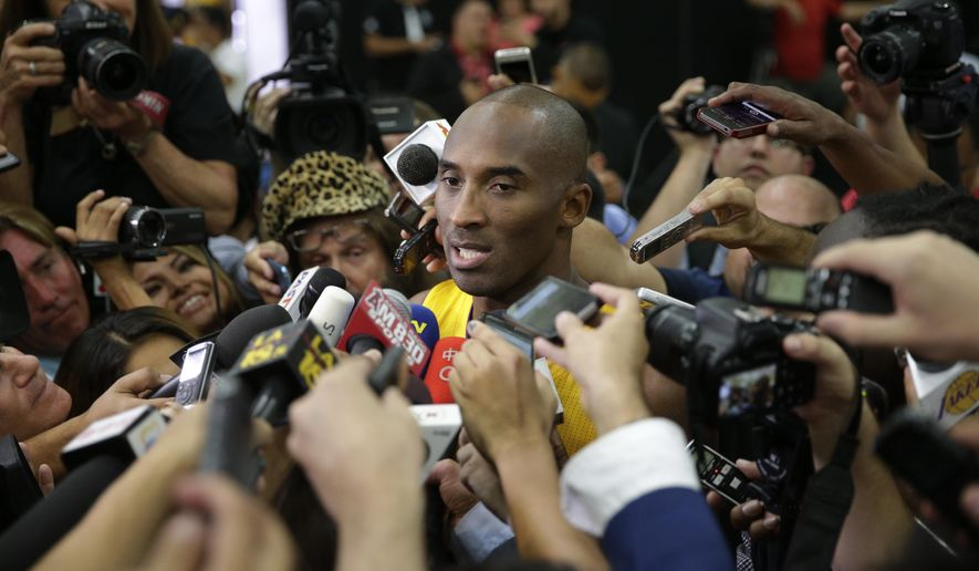 Los Angeles Lakers' Kobe Bryant is surrounded by reporters during the team's NBA basketball media day Monday, Sept. 29, 2014, in El Segundo, Calif. (AP Photo/Jae C. Hong)