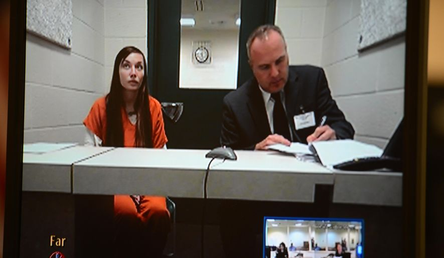 Cassie Nygren, left, is shown on a video monitor as she sits in a video conference room at the Brown County Jail with a public defender for her initial appearance after being arrested on drug charges, Monday, Sept. 29, 2014. (AP Photo/Green Bay Press-Gazette, Jim Matthews)