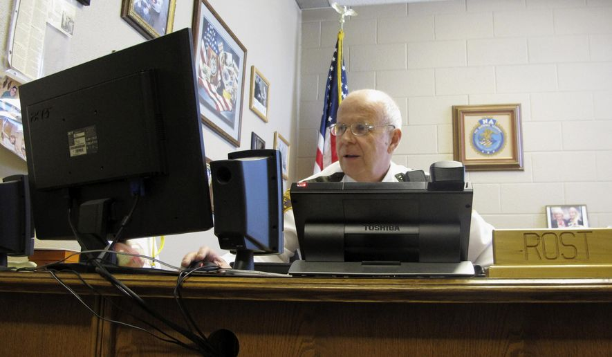 In this April 2, 2014 photo, Grand Forks County Sheriff Bob Rost is seen in his office in Grand Forks, N.D. Rost says the department flew its first nighttime unmanned aircraft mission early Sunday morning, Sept. 28, 2014, when four suspects fled after a traffic stop. The Federal Aviation Administration in March granted the department permission to fly a drone at night. (AP Photo/Dave Kolpack)