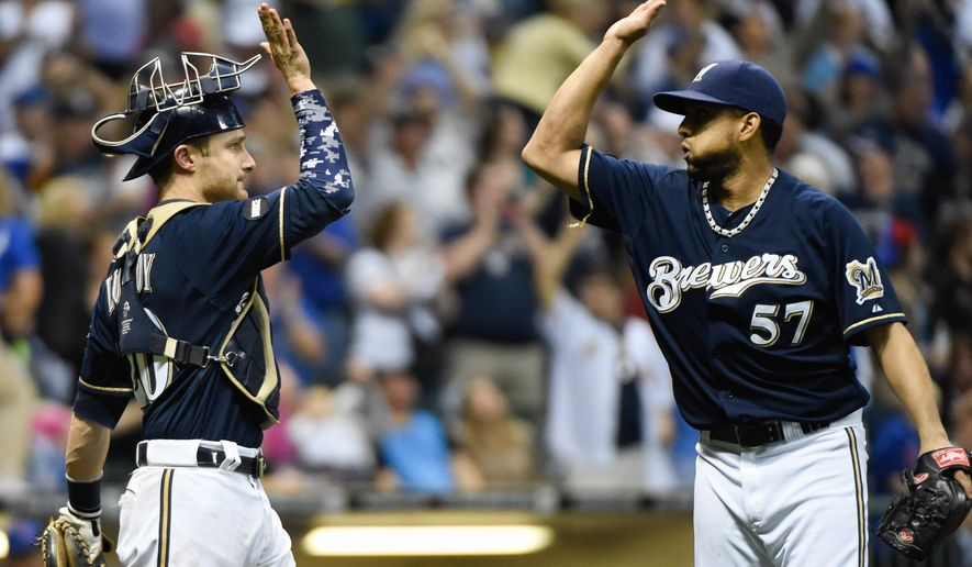 Milwaukee Brewers catcher Jonathan Lucroy, left, and pitcher Francisco Rodriguez, right, celebrate after the Brewers beat the Chicago Cubs 2-1  Saturday, Sept. 27, 2014, in Milwaukee. (AP Photo/Benny Sieu)