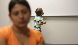 FILE - In this Sept. 10, 2014, file photo, an unidentified immigrant from Guatemala who declined to give her name, is interviewed, while her son paints on a whiteboard at the Artesia Family Residential Center, a federal detention facility for undocumented immigrant mothers and children in Artesia, N.M. A surge of cases involving immigrants from Central America has backed up federal courts and U.S. Immigration and Customs Enforcement. The cases have been moved to Denver by judges in Arlington, Virginia. Officials say it makes more sense to hold the proceedings in the same time zone as the detention center. Hearings are being held by video from Artesia, N.M. starting on Monday, Sept. 29. (AP Photo/Juan Carlos Llorca)